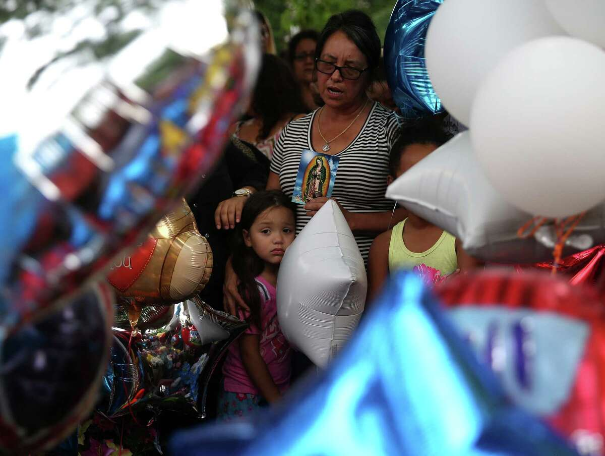 Neighbors and family members gather at a vigil on Wednesday honoring 11-year-old Josue Flores, who was stabbed to death while walking home from school on Tuesday.