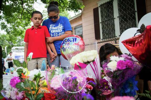 Beatrice Salazar and her son a Marshall Middle School student, Eli Renteria, 8, say a prayer at the place where Josue Flores, 11, was stabbed to death on Tuesday. Like Renteria, Flores was a Marshall Middle School student. Wednesday, May 18, 2016, in Houston. ( Marie D. De Jesus / Houston Chronicle )