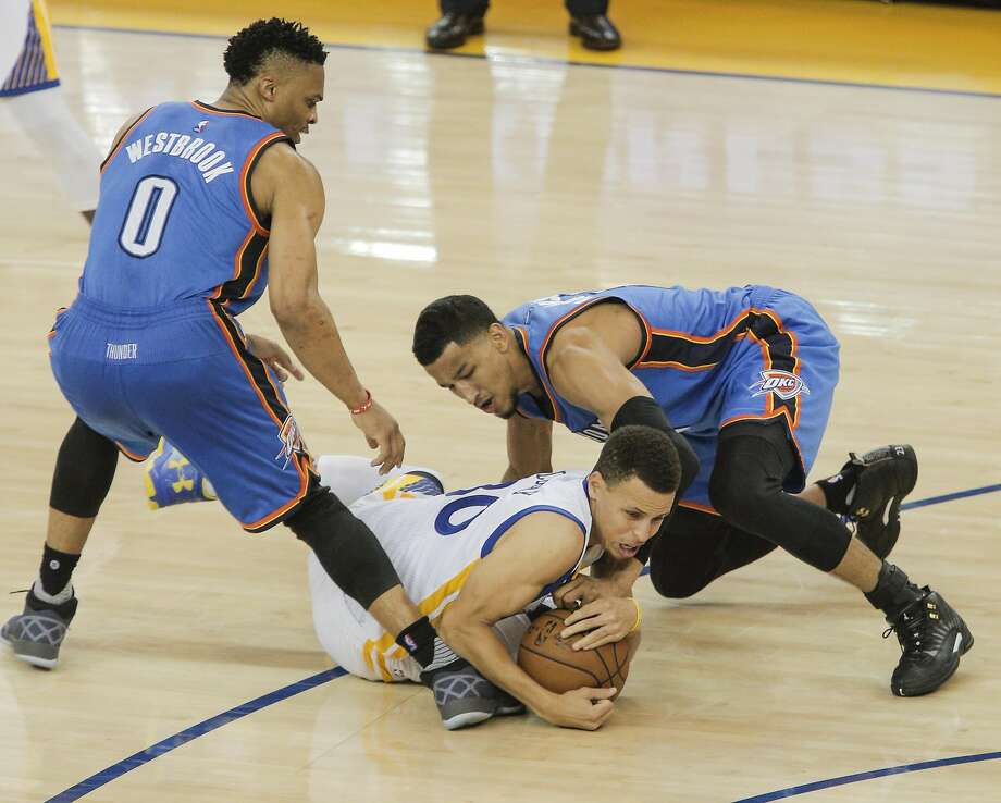 Golden State Warriors' Stephen Curry tries to keep a loose ball from Oklahoma City Thunders' Andre Roberson and Russell Westbrook in the third quarter during Game 2 of the NBA Western Conference Finals at Oracle Arena on Wednesday, May 18, 2016 in Oakland, Calif. Photo: Carlos Avila Gonzalez, The Chronicle