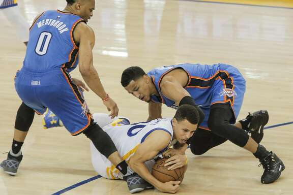 Golden State Warriors� Stephen Curry tries to keep a loose ball from Oklahoma City Thunders� Andre Roberson and Russell Westbrook in the third quarter during Game 2 of the NBA Western Conference Finals at Oracle Arena on Wednesday, May 18, 2016 in Oakland, Calif.