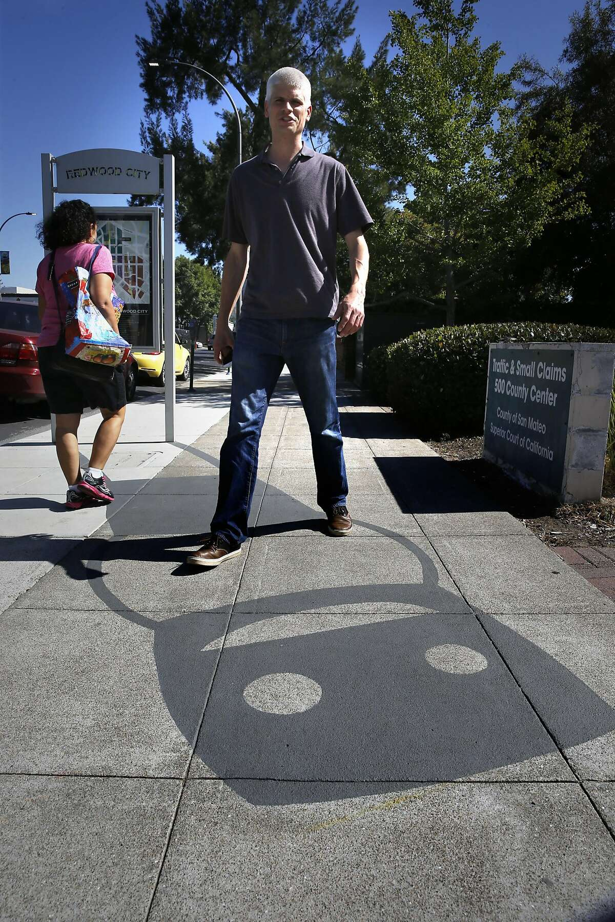 Damon Belanger, on Wed. May 18, 2016, next to one of his creations of shadow art he calls Mr. RWC. Belanger has created a series of paintings on the sidewalks of downtown Redwood City, California, that resemble the shadows thrown off from lamp posts, fire hydrants, mail boxes and bike racks.