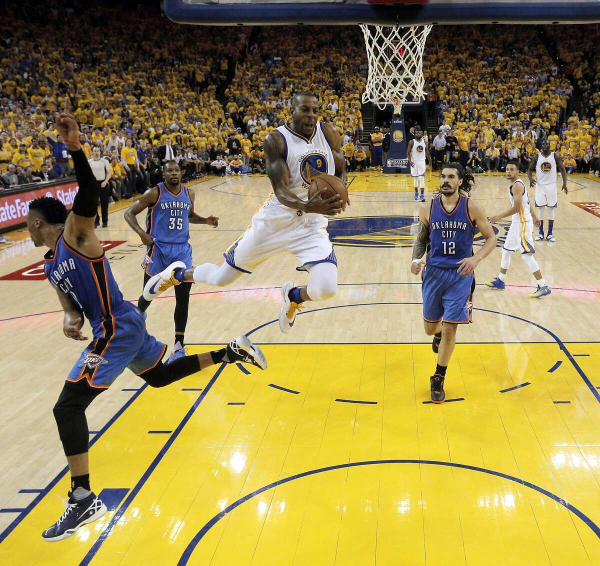 Andre Iguodala (9) is fouled by Russell Westbrook (0) in the first half as the Golden State Warriors played the Oklahoma City Thunder in Game 2 of the Western Conference Finals at Oracle Arena in Oakland, Calif., on Wednesday, May 18, 2016.