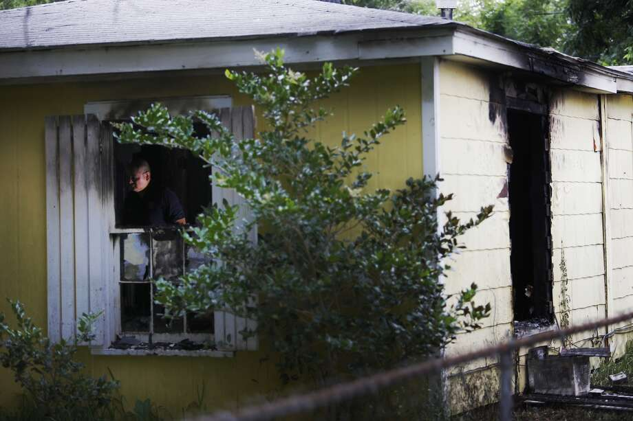 Firefighters look for hot spots Thursday May 19, 2016, at a house fire in the 500 block of Morrell Street in Baytown that sent two people to the hospital. (Houston Chronicle/Michael Ciaglo)
