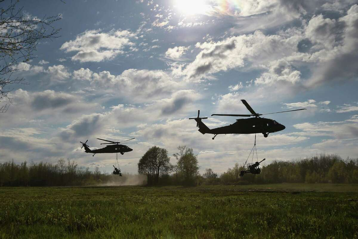FORT DRUM, NY - MAY 18: Blackhawk helicopters slingload 105mm Howitzers into place during a training exercise for future conflicts on May 18, 2016 at Fort Drum, New York. Members of the 10th Mountain Division Alpha Battery 3-6 Field Artillery staged an aerial assault and fired the guns, before flying them back out. Although most U.S. combat forces have been withdrawn from the continuing wars in Iraq and Afghanistan, the troops are on near-constant training exercises for future deployments. (Photo by John Moore/Getty Images)