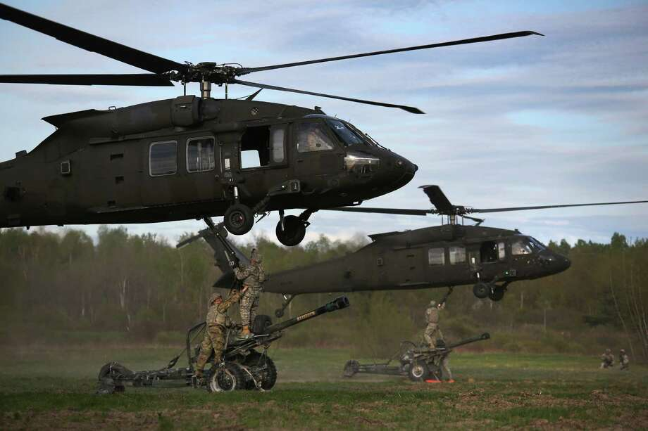 The 10th Mountain Division in Fort Drum is planning a week of aviation exercises over the next week. In this photograph, the 10th Mountain Division soldiers hook their 105mm Howitzers to Blackhawk helicopters while on a training mission for future deployments on May 18, 2016 at Fort Drum, New York. Members of Alpha Battery 3-6 Field Artillery staged an aerial assault and fired the guns, before flying them back out. Although most U.S. combat forces have been withdrawn from the continuing wars in Iraq and Afghanistan, the troops are on near-constant training exercises for future deployments.  (Photo by John Moore/Getty Images) Photo: John Moore / 2016 Getty Images
