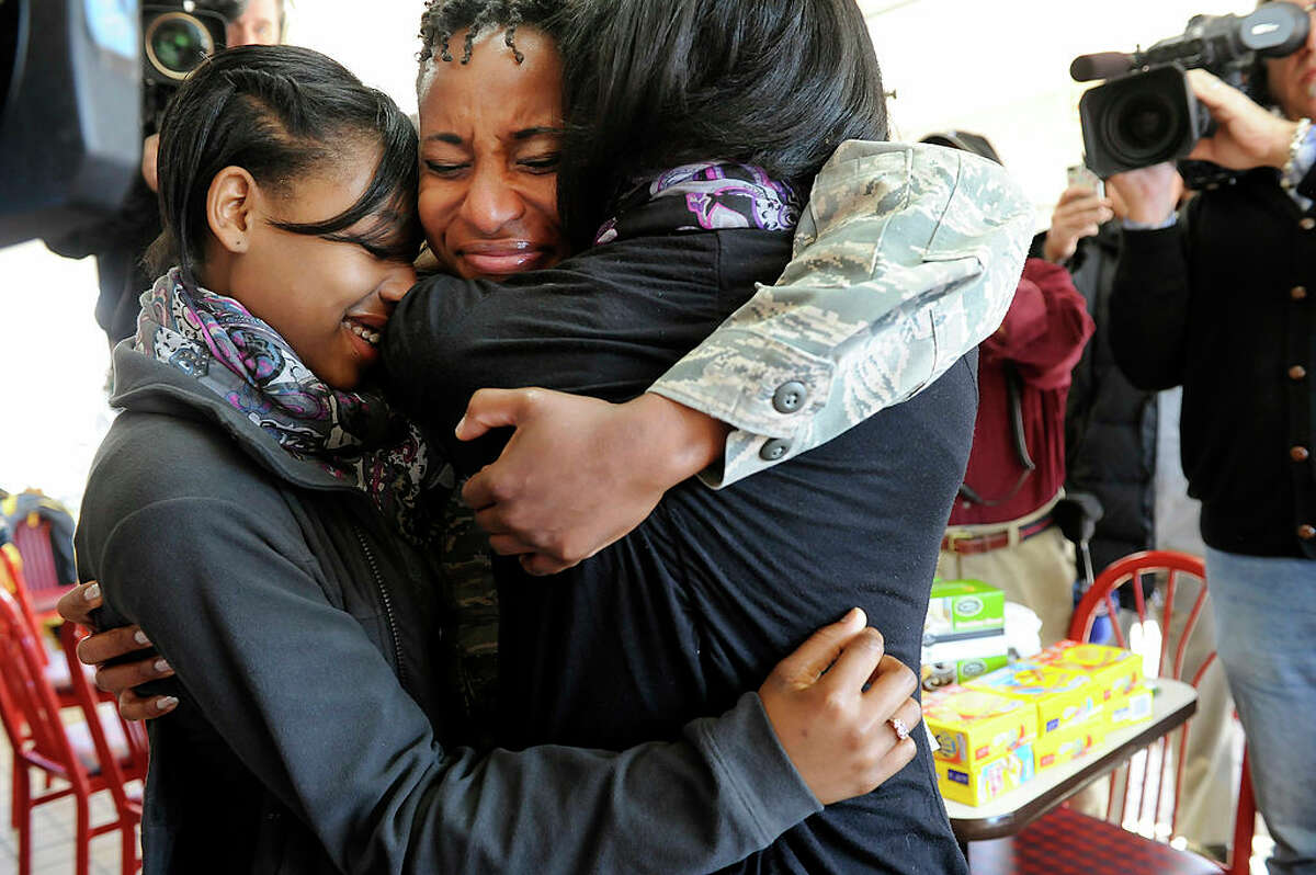 Air Force Captain Cherissa Jackson, center, surprises her 17-year-old fraternal twin daughters, Anita Lee, left, and Ashley Lee, right, at the Kentucky Fried Chicken on North Frederick Ave. on Tuesday January 10, 2012, in Gaithersburg, MD. Jackson, who is a critical care nurse was returning from serving in Afghanistan. KFC also surprised Captain Jackson by flying in her family from South Carolina and Florida. Anita and Ashley were presented with college scholarships of $20,000 each from KFC. The girls thought they were at KFC to prepare gift boxes for their mother's platoon.