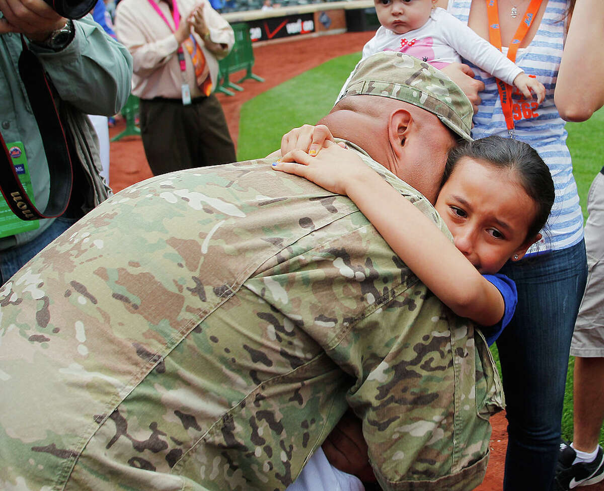 Sgt. Wilson Caro of the US Army is reunited with his daughter Ciara Luna Caro before the game between the New York Mets and the Miami Marlins at Citi Field on June 8, 2013, in the Flushing neighborhood of the Queens borough of New York City. Sgt. Caro was flown in from Afghanistan by the New York Mets for the reunion.