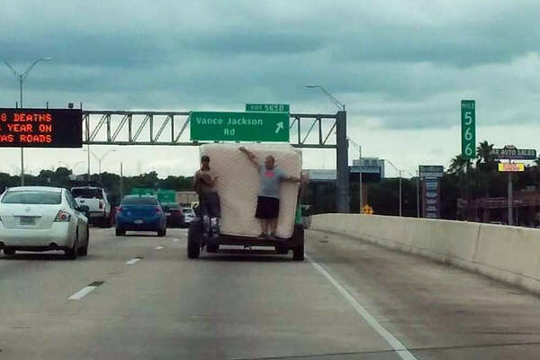 A photo taken by Roxanne Garza and Serrah Hernandez on May 19, 2016, shows two identified men using their bodies to restrain mattresses on a trailer traveling on Interstate 10.