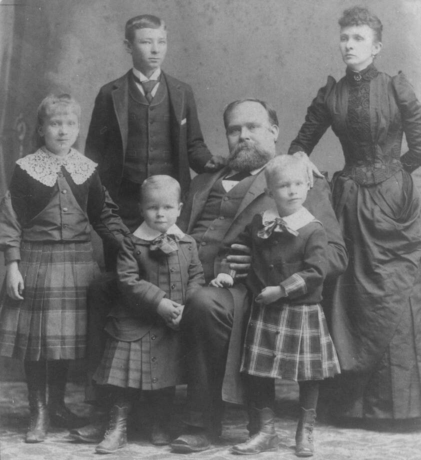 James Stephen Hogg dominates this family portrait of 1891, during the early days of his tenure as governor of Texas.  At left is Ima, with Will Hogg and Mrs. Hogg standing behind the governor.  Tom Hogg stands between his father's knees, and Mike Hogg is beside him.  HOUCHRON CAPTION (12/28/1998):  A late-19th century photograph of the Hogg family shows, from left, Ima, William C., Thomas E., Gov. James S., Michael and Sarah Stinson Hogg. / handout