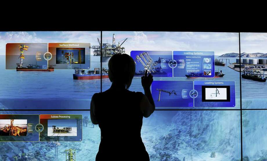 A FMC Technologies Inc. employee checks an interactive mural at the company's booth during the 2016 Offshore Technology Conference in Houston earlier this month. FMC Technologies and Technip, both oil services companies, announced Thursday that they planned to merge in a $13 billion transaction. Photo: Aaron Sprecher /Bloomberg News / © 2016 Bloomberg Finance LP