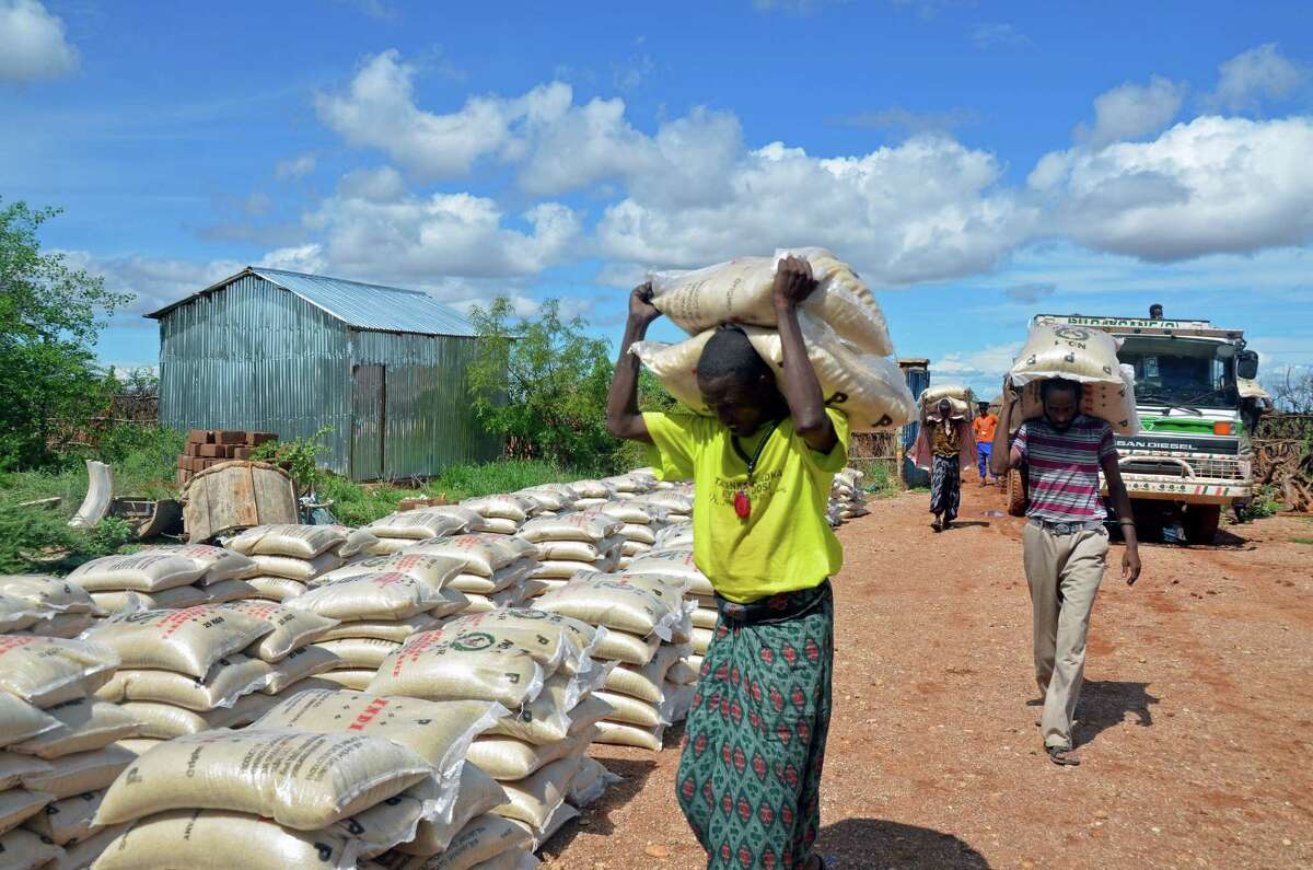 Village men unloading 55-pound sacks of rice in Denan, Ethiopia.