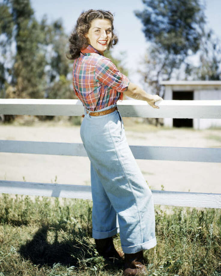1950: In 1934, Levi's introduced their first pair of women's jeans, which were worn mostly by women who lived on farms and ranches. Sixteen year later, jeans were still linked with that western vibe—but they also had an air of coolness to them. Thanks to Hollywood's popular western films and cowboys being very much in vogue, jeans started appearing in many movies and publicity shots, like this one of actress Jane Russell. Photo: Getty Images