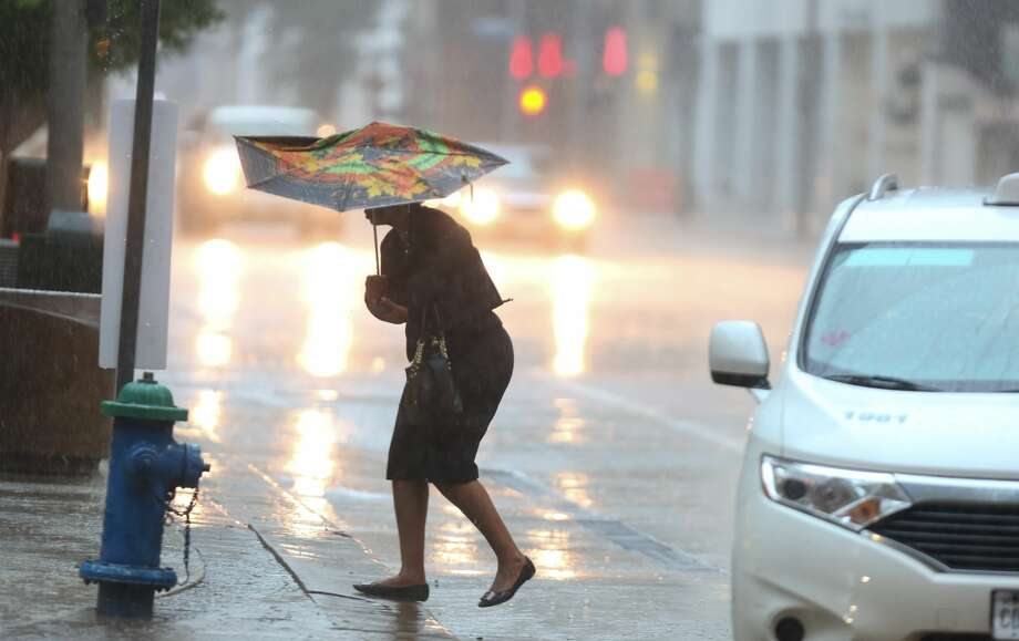 A pedestrian struggles against driving rain and strong winds at San Jacinto and McKinney downtown Houston, Thursday, May 19, 2016. Photo: Steve Gonzales / Houston Chronicle
