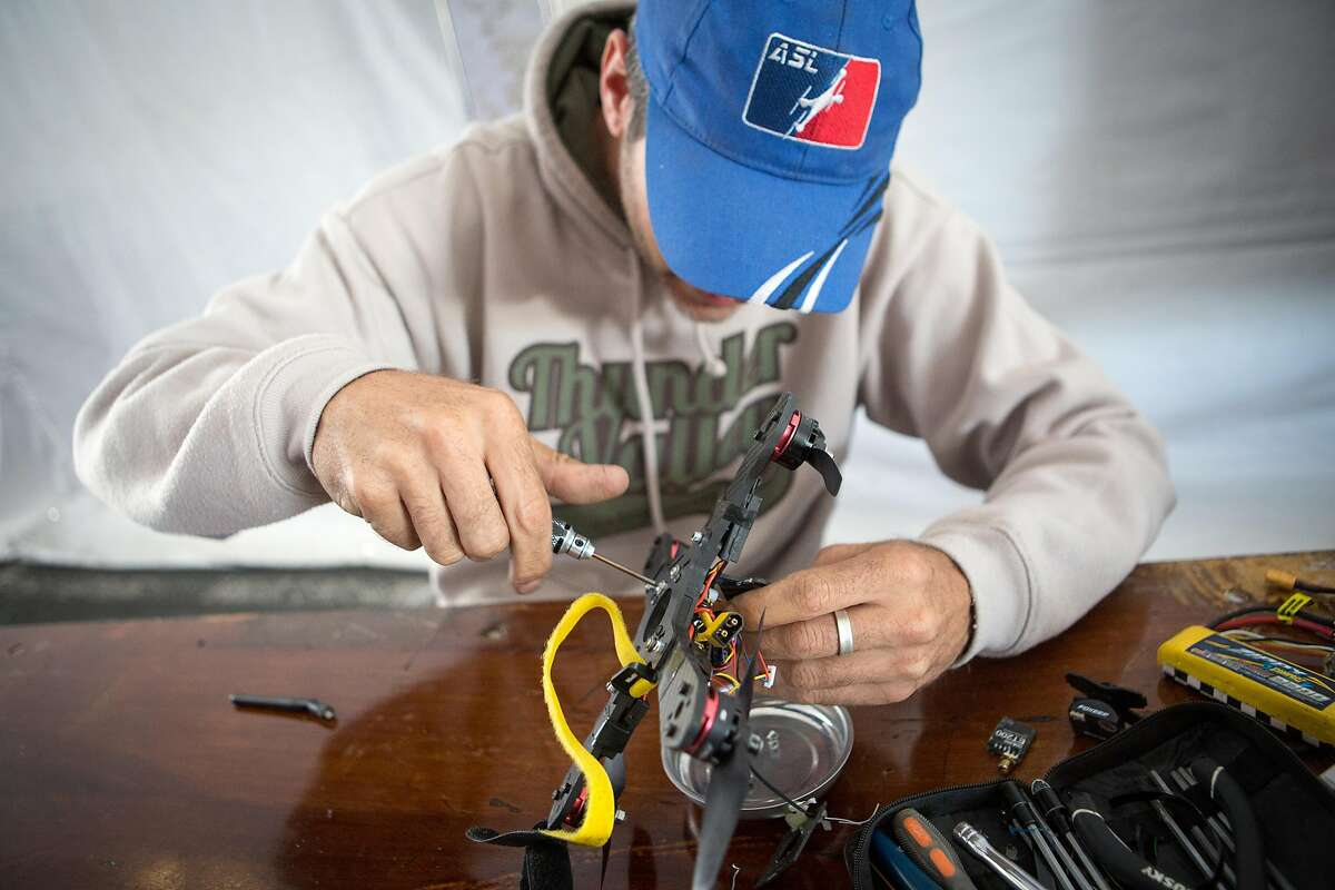 Jason Bouslaugh fine tunes his racing drone in the Drone Racing Tent as set up continues at the San Mateo Event Center for Maker Faire on Thursday, May 19, 2016.
