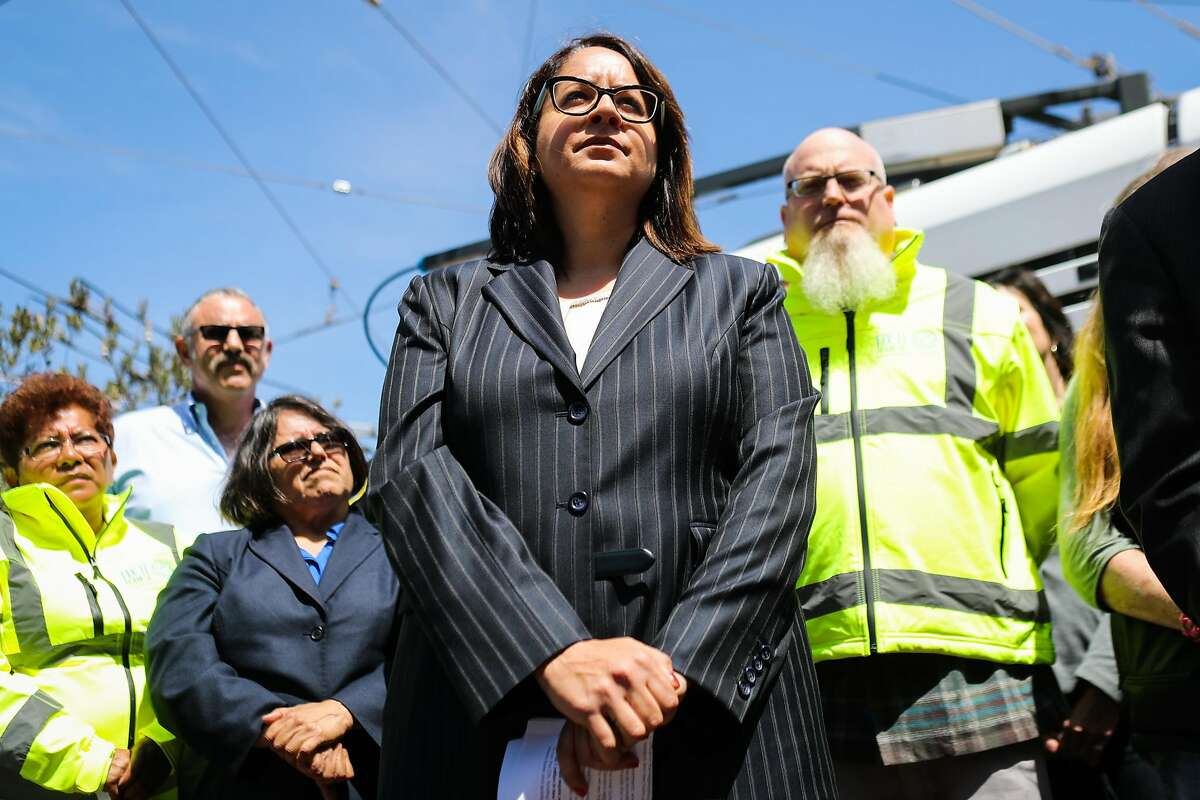 Sandra Zuniga (center), the director of the new fix-it teams listens as Mayor Ed Lee speaks at a press conference, in San Francisco, California, on Thursday, May 19, 2016.