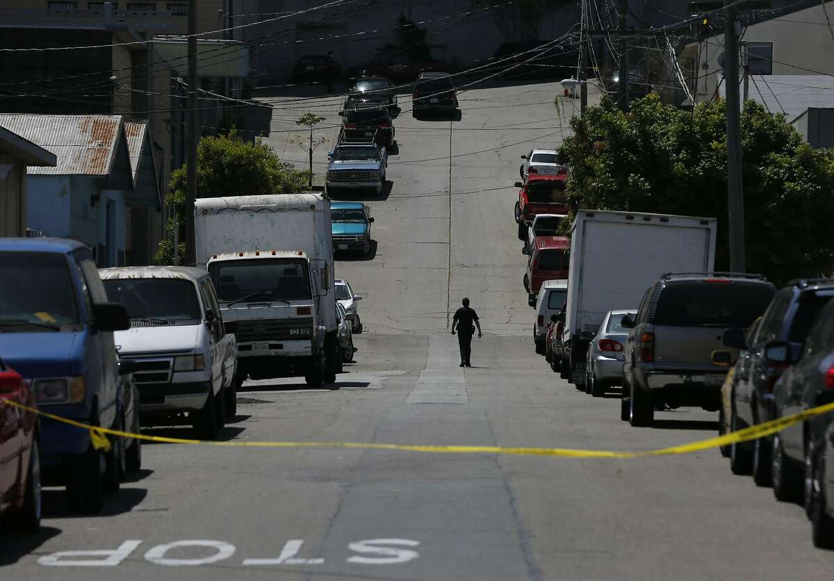 A police officer walks down Elmira Street towards the scene of an officer involved shooting that ended in the death of the woman who was shot May 19, 2016 in San Francisco, Calif. Police officers began pursuing a car that came up as stolen in their system and after the woman crashed the car into a parked vehicle, she was shot once while officers tried to remove her from the car and she died from the gunshot wound.