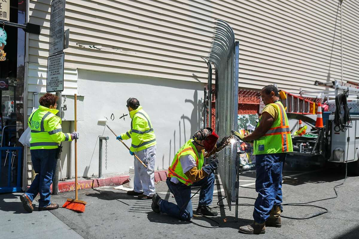 A group of fix-it teams working to clean up graffiti and fix a door in the Castro neighborhood, in San Francisco, California, on Thursday, May 19, 2016.