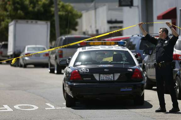 A police officer lifts up police tape to allow a squad car into the scene of an officer involved shooting on Elmira Street that ended in the death of the woman who was shot   May 19, 2016 in San Francisco, Calif. Police officers began pursuing a car that came up as stolen in their system and after the woman crashed the car into a parked vehicle, she was shot once while officers tried to remove her from the car and she died from the gunshot wound.