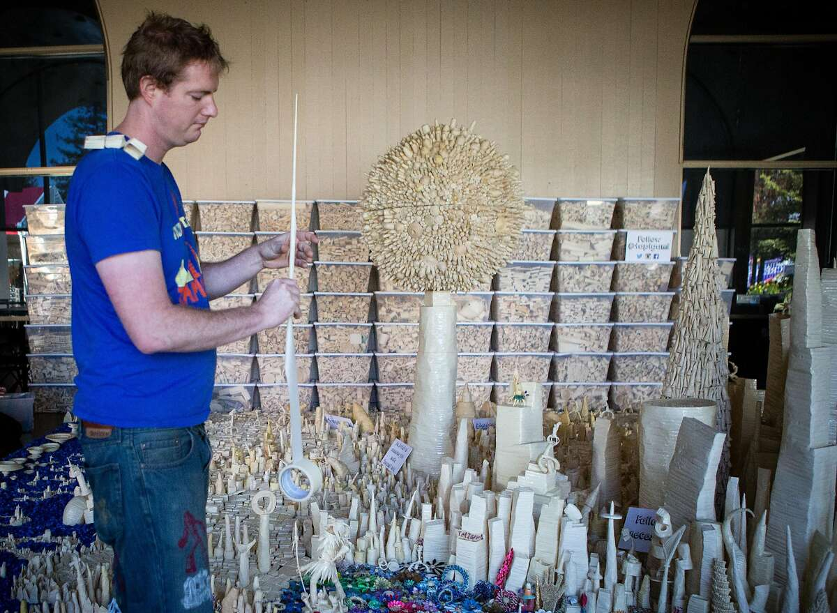"""Maker Danny Scheible puts the final touches on """"Tape-polis"""", an 11 year project made completely out of masking tape, a process that he calls """"tapigami"""" at the San Mateo Event Center for Maker Faire on Thursday, May 19, 2016."""