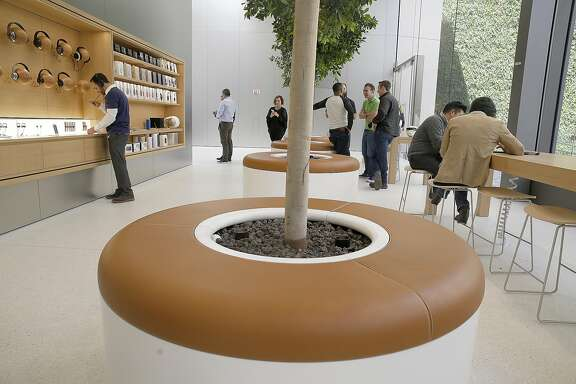 The new Apple building on Post at Stockton streets has a media tour showing  genius bar customer lounging with leather seats, displays, and trees in San Francisco, California, on thursday, may 19, 2016.