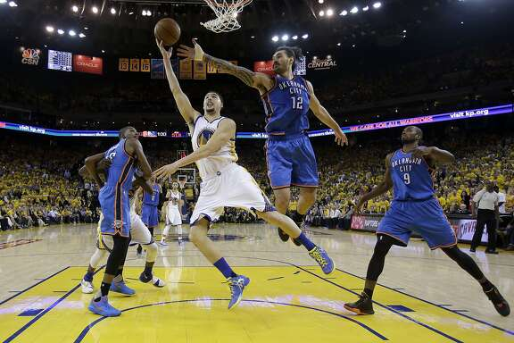 Golden State Warriors guard Klay Thompson, center, shoots between Oklahoma City Thunder players Kevin Durant, left, Steven Adams (12) and Serge Ibaka (9) during the second half of Game 1 of the NBA basketball Western Conference finals in Oakland, Calif., Monday, May 16, 2016. The Thunder won 108-102. (AP Photo/Marcio Jose Sanchez)