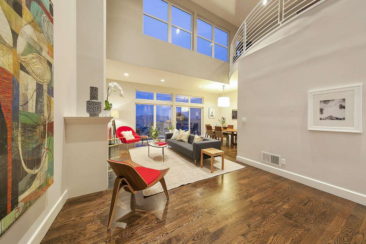 The open floor plan integrates the living and dining rooms beneath a towering ceiling.