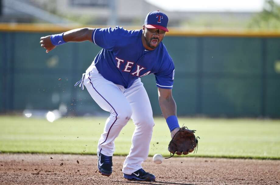 Seattle Seahawks quarterback Russell Wilson works out at second base with the Texas Rangers prior to a Rangers spring training baseball game against the San Diego Padres, Saturday, March 28, 2015, in Surprise, Ariz.  (AP Photo/Lenny Ignelzi) Photo: AP