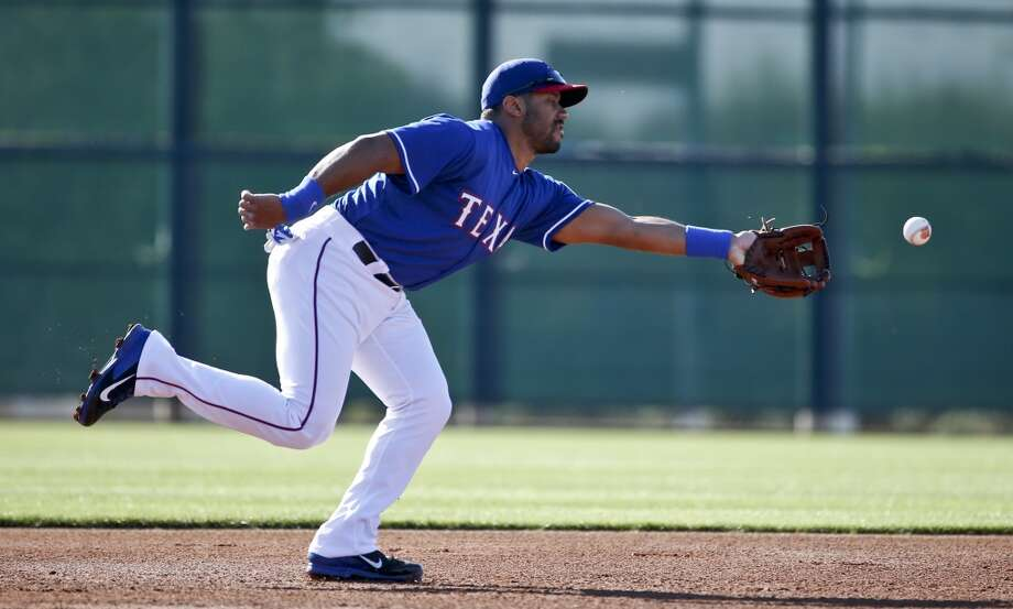 Seattle Seahawks quarterback Russell Wilson works out at shortstop with the Texas Rangers prior to a Rangers spring training baseball game against the San Diego Padres, Saturday, March 28, 2015, in Surprise, Ariz.  (AP Photo/Lenny Ignelzi) Photo: AP