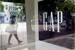FILE - In this Saturday, Aug. 15, 2015, file photo, a pedestrian walks past a Gap store in Miami. The Gap Inc. reports earnings on Thursday, May 19, 2016. (AP Photo/Lynne Sladky, File)