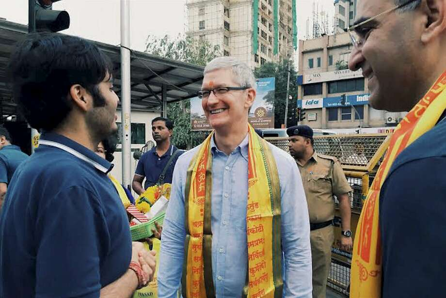 Cook, center,  interacts with Anant Ambani, left, son of industrialist Mukesh Ambani, outside Siddhivinayak Hindu Temple  in Mumbai, India, Wednesday, May 18, 2016. Apple India head Sanjay Kaul is on right. Apple will set up an app design and development center in southern India, the company announced Wednesday, shortly after company chief Tim Cook arrived in the country on his first visit. (Press Trust of India via AP) Photo: Associated Press