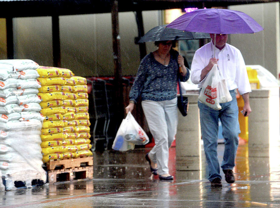 Shoppers take shelter from the rain while making their way in and out of the HEB Plus on Dowlen Road as a rainstorm passes through the region Thursday. The storm brought with it multiple lightning strikes and cancelled outdoor sporting events. Photo taken Thursday, May 19, 2016 Kim Brent/The Enterprise Photo: Kim Brent / Beaumont Enterprise