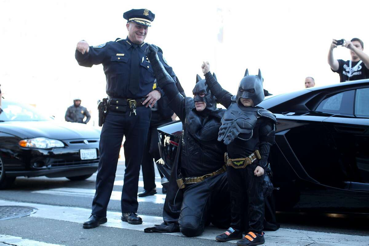 Miles Scott, 5, dressed as Batkid, right, along with Batman and Police Chief Greg Suhr fist pump to an adoring crowd of thousands during a Make-a-Wish benefit where Miles Scott, 5 saves Gotham as Batkid in San Francisco, Calif., Friday November 16, 2013.