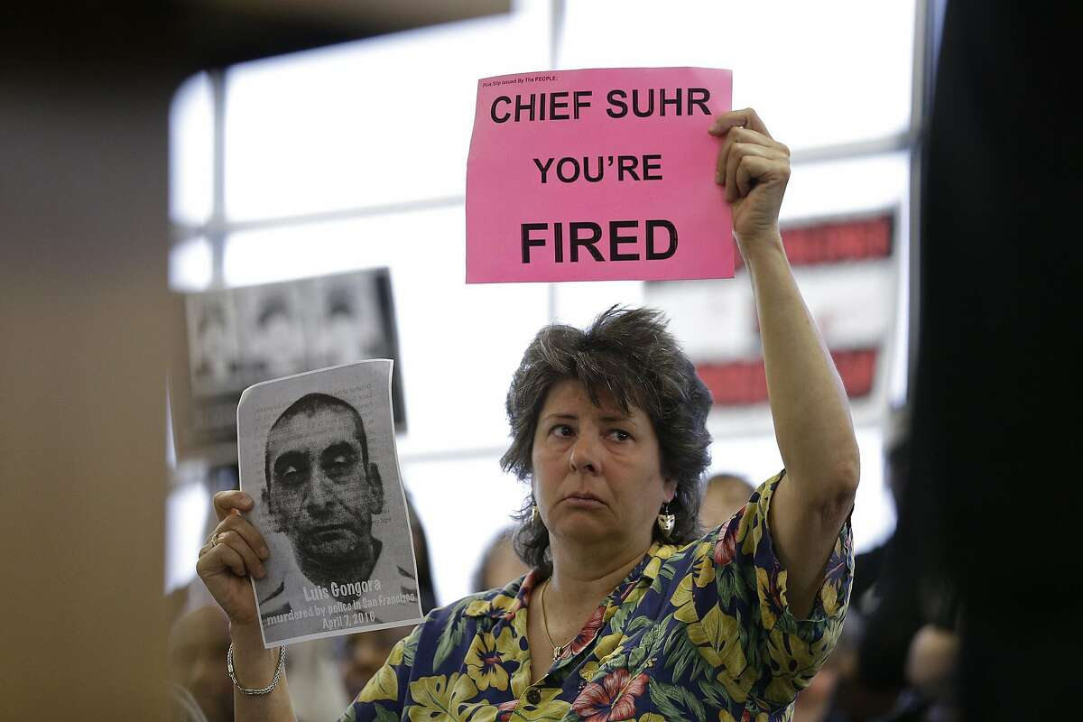 A woman holds up a picture of Luis Gongora and a sign against San Francisco police chief Greg Suhr during a town hall meeting to provide the Mission District neighborhood with an update on the investigation of an officer involved shooting Wednesday, April 13, 2016, in San Francisco. The meeting came after 45-year-old Luis Gongora was shot and killed by police at a homeless encampment on Thursday, April 7, 2016.