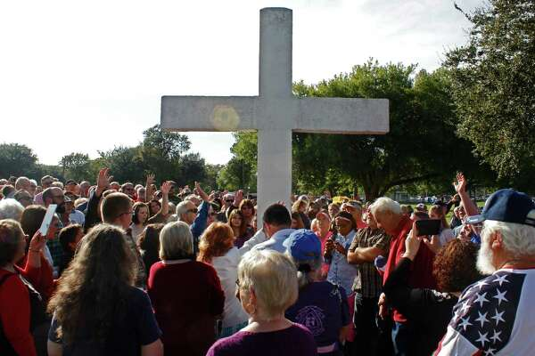 A group gathers around the cross for prayer at Riverfront Park in Port Neches during a vigil on Sunday.