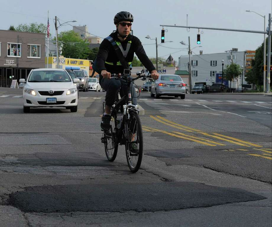 """Above left, John Track, of Stamford, navigates down Greenwich Avenue in Stamford on Friday as he commutes to work. Track, who is an avid bike rider, competes with drivers and road obstructions during his commute to his job on his bicycle. Above right, Ronald Morse and his fiancée, Anne Friedman, participate in """"Bike to Work Day"""" in Stamford on Friday. Photo: Matthew Brown / Hearst Connecticut Media / Stamford Advocate"""