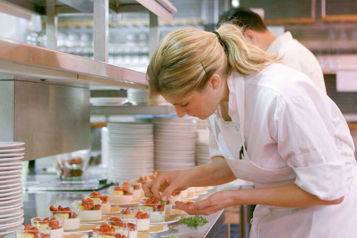 A pastry chef garnishes panna cotta at the Four Seasons restaurant in New  York, which is closing in July.