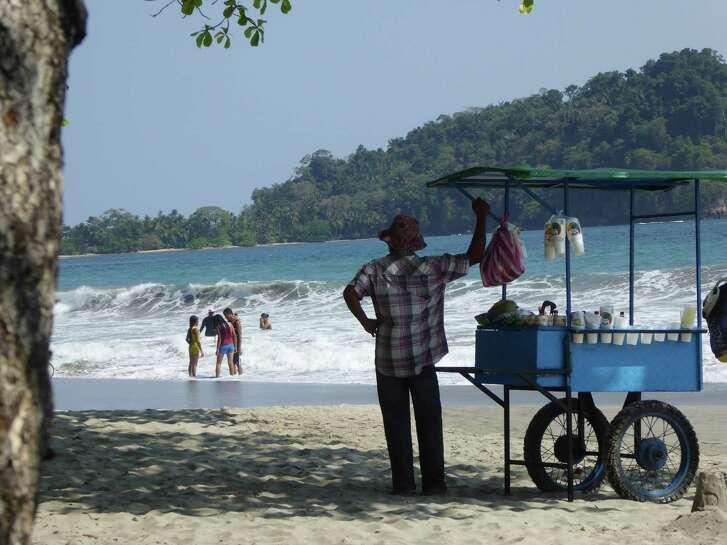 A vendor sells coconut drinks at a beach at Manuel Antonio, Costa Rica.
