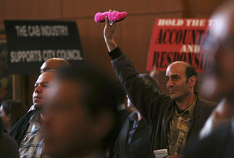 David Albion holds up a Lyft logo as supporters and opponents of the proposed  San Antonio City Council ride-share ordinance fill the chambers, Thursday, Dec. 11, 2014. The city is proposing an ordinance that will severely affect ride-share companies like Uber and Lyft. Photo: JERRY LARA, San Antonio Express-News