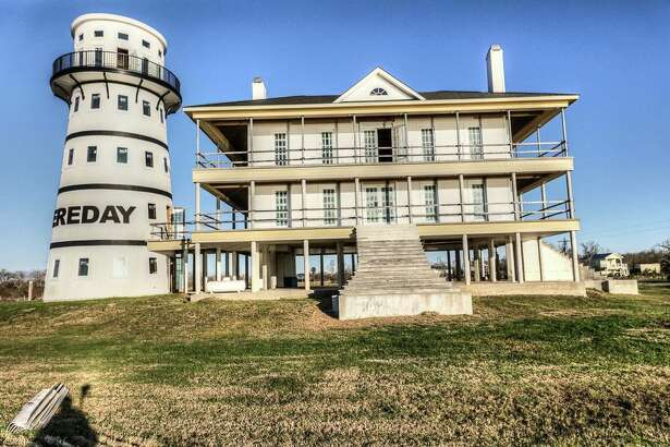 The property at 111 Poncho in Anahuac, Texas features a main house and a lighthouse.