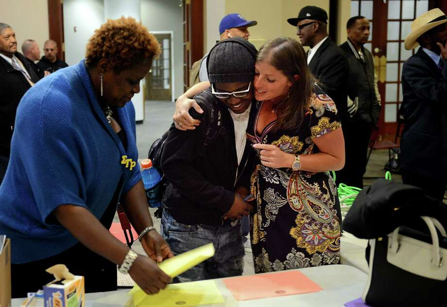Andrea Weller, a coordinator with My Brother's Keeper, hugs student Bassick High student Samuel Profit, before the start of the Agents of Change Workshop at the Margaret E. Morton Government Center in Bridgeport, Conn., on Tuesday May 17, 2016. The workshop explores how street violence and gangs destroy a community. Thirty young men of color attend the nine week course to learn about violence prevention. Photo: Christian Abraham / Christian Abraham / Connecticut Post