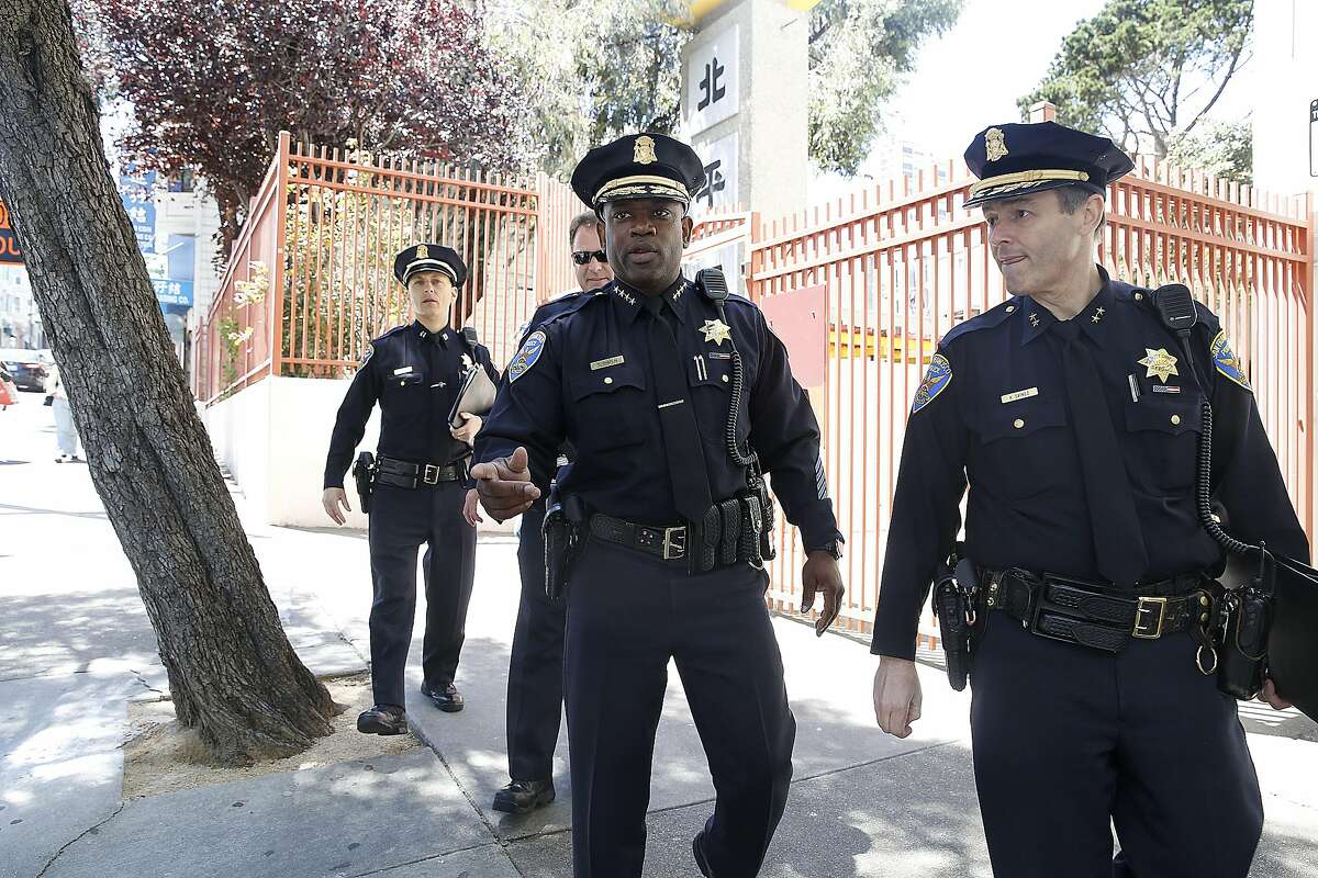 Acting Chief Toney Chaplin (middle) talks with deputy chief Hector Sainez while leaving the Ping Yuen center in Chinatown in San Francisco, California, on Friday, May 20, 2016.