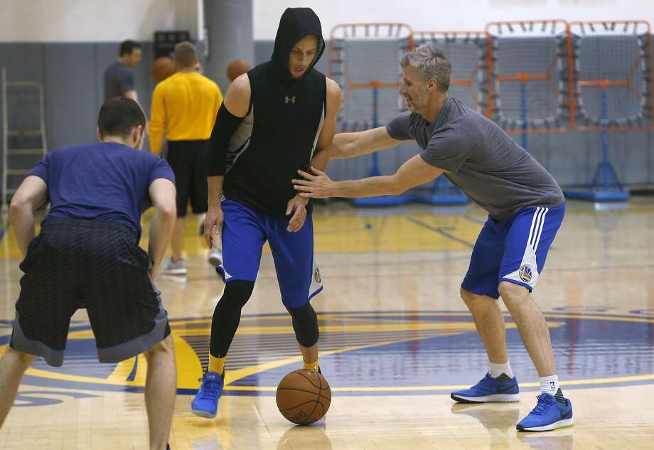 Even a two-time MVP still needs coaching as Nick U'Ren, left, and Bruce Fraser show while working with Stephen Curry at the team's practice facility on Friday. Photo: Paul Chinn, The Chronicle