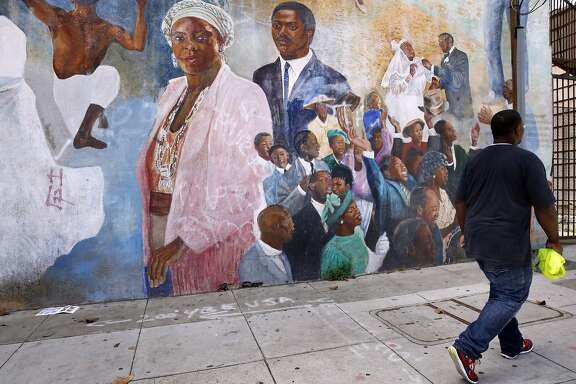 A man walks by a mural called Tuzuri Watu by Brooke Fancher on 3rd and Palou streets in the Bayview neighborhood May 20, 2016 in San Francisco, Calif.