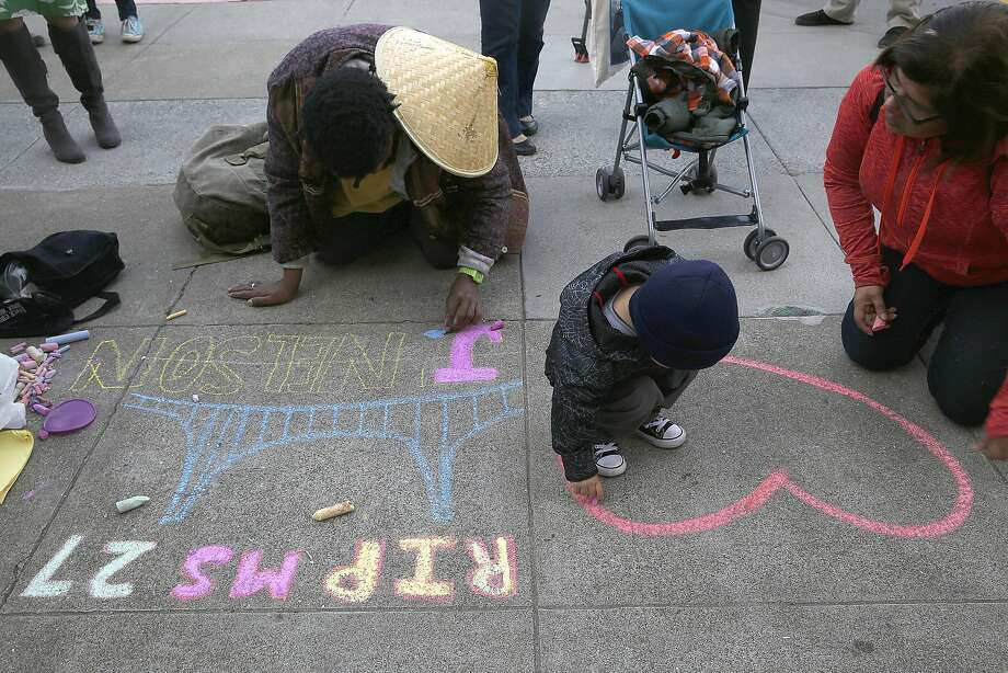 Charles Pitts (left), 2-year-old Benecio Rodriguez and Irene Araujo memorialize police shooting victims on the sidewalk in front of City Hall. Photo: Liz Hafalia, The Chronicle