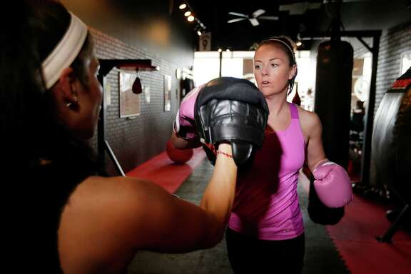 Maggie Gordon, right, gets kickboxing pointers from Crystal Saldivar at 9Round. Gordon worked out at nine other facilities during her two-week ClassPass trial offer.