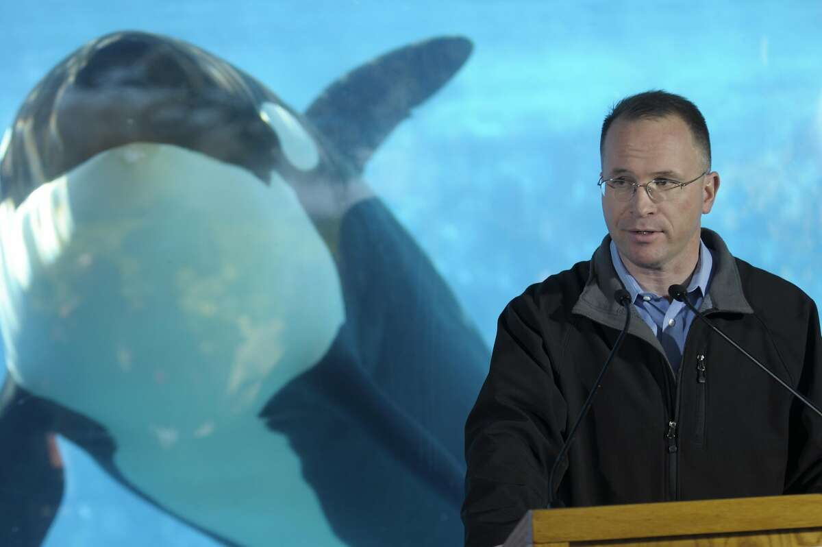 Jim Atchison, right, President & CEO of SeaWorld Parks & Entertainment, speaks during a news conference at the killer whale underwater viewing area of SeaWorld in Orlando, Fla., Friday, Feb. 26, 2010. SeaWorld will restart its killer whale shows this weekend after Tilikum, the largest orca in captivity, dragged a trainer to her death in the water at the Orlando park. (AP Photo/Phelan M. Ebenhack)
