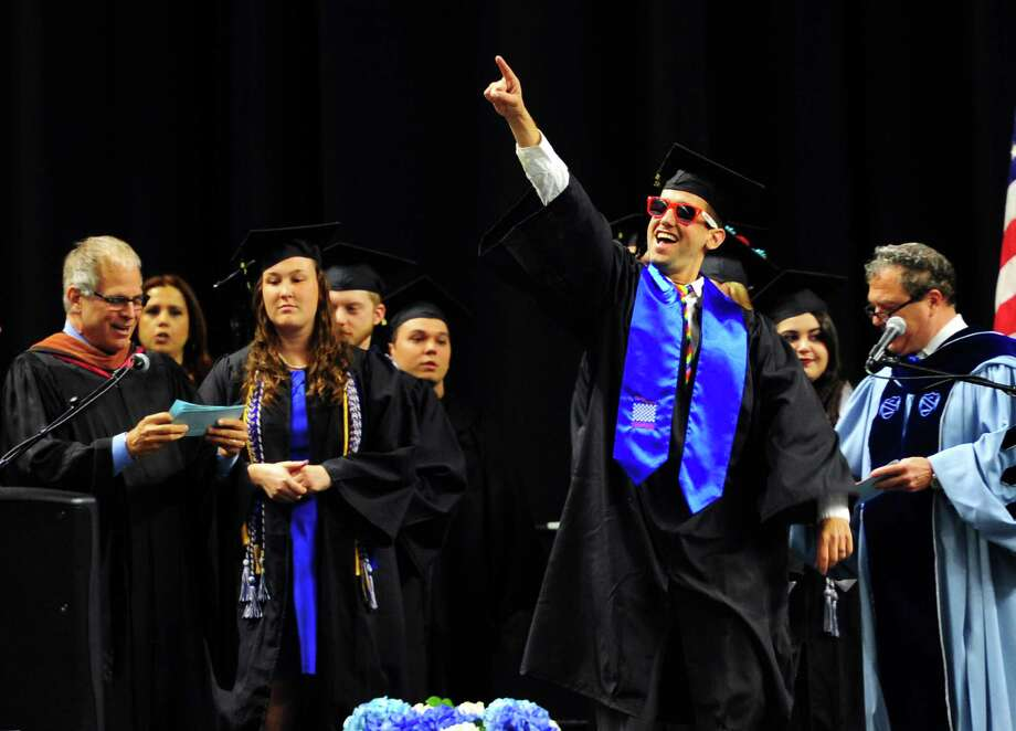 Jason Riddle, of Shelton, points to his family as he walks onstage to get his diploma during Southern Connecticut State University's Commencement 2016 Undergraduate Ceremony at the Arena at Harbor Yard in Bridgeport on Friday. Photo: Christian Abraham / Hearst Connecticut Media / Connecticut Post