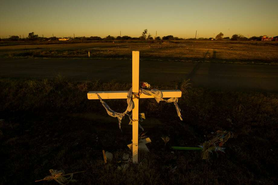 A memorial cross is planted in West near the spot where 15 people died, 