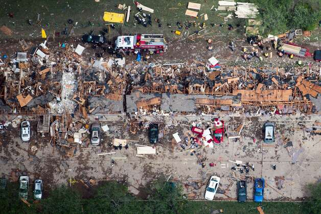 Law enforcement and rescue personnel search the damage to an apartment complex from the explosion of the West Fertilizer plant on Thursday, April 18, 2013, in West, Texas.  A massive explosion at the plant killed as many as 15 people and injured more than 160, officials said overnight.  ( Smiley N. Pool / Houston Chronicle ) Photo: Houston Chronicle