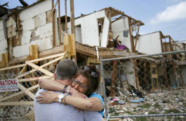 Shona Jupe, a resident of the apartment destroyed by the fertilizer plant explosion, hugs her friend as they met while she was visiting the site in West, Texas, on Friday, May 10, 2013. Jupe was at the front door when the West Fertilizer Co. explosion happened. Texas law enforcement officials on Friday launched a criminal investigation into the massive fertilizer plant explosion that killed 14 people last month, after weeks of largely treating the blast as an industrial accident. (AP Photo/The Dallas Morning News, Kye R. Lee)  MANDATORY CREDIT; MAGS OUT; TV OUT; INTERNET OUT; AP MEMBERS ONLY Photo: Associated Press